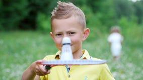 Het close-up, a-kind, een jongen, houdt een shuttle op een badmintonracket, werpt het en raakt het stock videobeelden