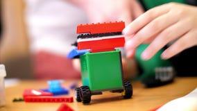 Het close-up, kinderen` s handen houdt een multicolored kleine die auto van een ontwerper wordt geassembleerd stock video