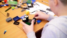 Het close-up, kinderen` s handen houdt een multicolored kleine die robot, machine, van een ontwerper wordt geassembleerd de kinde stock video