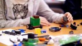 Het close-up, kinderen` s handen houdt een multicolored kleine die robot, machine, van een ontwerper wordt geassembleerd de kinde stock footage