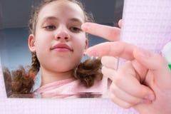 Het close-up, het meisje kijkt in de spiegel en houdt een lens op haar vinger om visie te verbeteren stock foto