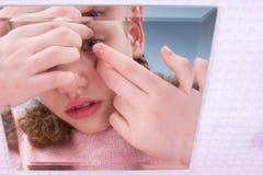 Het close-up, het meisje kijkt in de spiegel en zet op lenzen om visie te verbeteren royalty-vrije stock foto