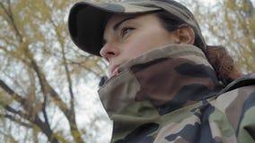 Het close-up, mooi meisje in camouflage GLB werpt een staaf in de rivier op een mistige ochtend stock footage