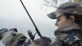 Het close-up, mooi visstermeisje in camouflagekostuum trekt hengel van de rivier en controleert het lokmiddel op de haak stock video