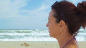 Het close-up, mooie vrouw bekijkt de overzeese zitting op het strand stock footage