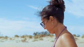 Het close-up, mooie vrouw in de zwempakzitting op het strand kleedt zonnebril stock videobeelden