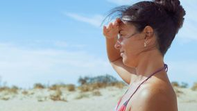 Het close-up, mooie vrouw in het zwempak zit op het strand en kijkt weg sluitend de hand een mening van de zon stock videobeelden