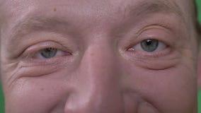 Het close-up oog-portret van de Kaukasische mens op middelbare leeftijd met baard glimlacht in camera op groene achtergrond stock video