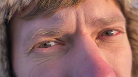 Het close-up oog-portret van ontdekkingsreiziger op middelbare leeftijd in kap en laag draait aan camera en horloges calmly in ca stock footage