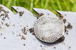Het close-up op oud, gehamerd zilveren die muntstuk op een schop wordt blootgesteld, in het leven wordt gevonden graaft door meta stock foto's