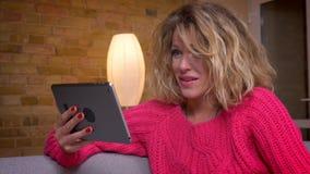 Het close-up schoot blondehuisvrouw in het roze sweater letten op in tablet met gelukkig vermaak in comfortabele huisatmosfeer stock video