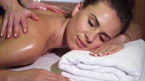 Het close-up toont het ontspannen gezicht van een meisje dat een achtermassage heeft stock videobeelden