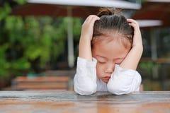 Het close-up van aanbiddelijk weinig Aziatisch kindmeisje drukte teleurstelling of ongenoegen op de houten lijst uit royalty-vrije stock foto's