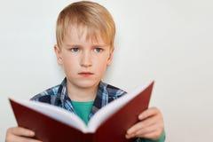 Het close-up van aantrekkelijke schooljongen met blauwe ogen en blond haar kleedde zich in gecontroleerd overhemd houdend een boe royalty-vrije stock fotografie