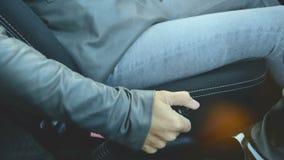 Het close-up van het actiemeisje krijgt in de auto en de draaien van de handremhefboom in de auto alvorens overal te gaan E stock video