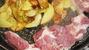 Het close-up van bacon en de gesneden aardappels zijn gebraden in pan op fornuis stock footage