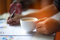 Het close-up van bedrijfsmensenholding vormt koffie tot een kom royalty-vrije stock foto's