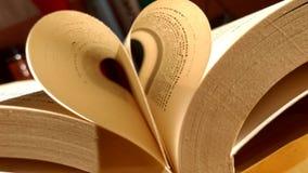 Het close-up van het boek opende, dat het boekblad in een selectieve nadruk van de hartvorm en een ondiepe velddiepte rolde stock fotografie