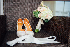 Het close-up van bruids boeket van rozen, huwelijk bloeit voor de ceremonie op het bed in een hotelruimte met witte schoenen Stock Foto's