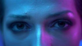 Het close-up van buitengewone mannequin met schittert make-up in kleurrijke neonlichten knipperend in camera in studio stock video