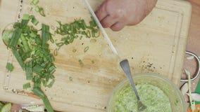 Het close-up van chef's overhandigt fijn het hakken, snijdend ruwe de lenteuien stock video