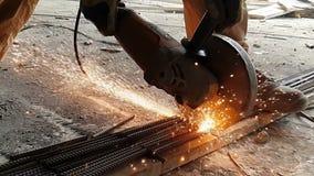 Het close-up van de Bulgaar snijdt metaal in langzame motie Vonkenvlieg uit van onder het wiel van de molen in langzame motie stock video