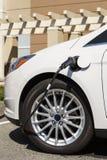 Het close-up van de elektrische die auto van het autovoertuig met kabel wordt gestopt in verbond met elektrische het laden post Stock Fotografie