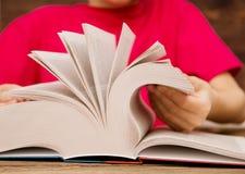 Het close-up van de hand op het boek gaat de pagina aan het volgende hoofdstuk draaien meisje die de pagina's van het boek doorbl stock afbeeldingen