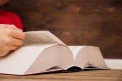 Het close-up van de hand op het boek gaat de pagina aan het volgende hoofdstuk draaien meisje die de pagina's van het boek doorbl stock foto's