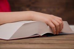 Het close-up van de hand op het boek gaat de pagina aan het volgende hoofdstuk draaien meisje die de pagina's van het boek doorbl stock afbeelding