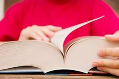 Het close-up van de hand op het boek gaat de pagina aan het volgende hoofdstuk draaien meisje die de pagina's van het boek doorbl stock fotografie