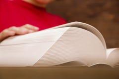 Het close-up van de hand op het boek gaat de pagina aan het volgende hoofdstuk draaien meisje die de pagina's van het boek doorbl royalty-vrije stock foto
