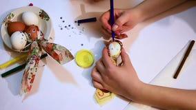 Het close-up van de handen van een meisje en een kind verfraaien een wit ei met een gekleurd servet en een glanzend lint en trekk stock videobeelden