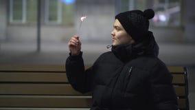 Het close-up van de jonge glimlachende mens in zwart de winterjasje en de gebreide hoedenzitting op de bank met bengals steken in stock videobeelden