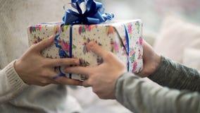 Het close-up van de mens gaat gift tot vrouw over De close-upkerel gaf zijn meisjekerstmis of van het nieuwe jaar gift De feestel stock foto