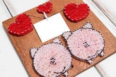 Het close-up van de Raad met spijkers verwondt met draden in de vorm van harten en varkens en een stuk van document op een draad royalty-vrije stock foto