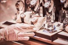 Het close-up van de verkoper dient handschoenen in toont het horloge van de exclusieve mensen van de nieuwe inzameling stock foto