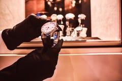 Het close-up van de verkoper dient handschoenen in toont het horloge van de exclusieve mensen van de nieuwe inzameling royalty-vrije stock afbeeldingen