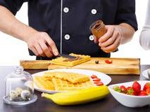Het close-up van de vlek van chef-kok` s handen met een mes kookte condens op wafels stock afbeeldingen