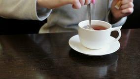 Het close-up van de vrouwen` s handen giet suiker in een Kop thee en beweegt het met een lepel stock footage