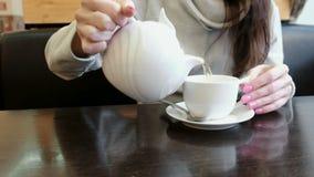 Het close-up van de vrouwen` s handen giet thee van de theepot in een mok Zachte nadruk stock videobeelden
