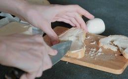 Het close-up van de vrouwen` s handen smeert boter op een stuk van brood, gebruikend een mes Het maken van een Sandwich stock afbeelding