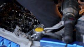 Het close-up van de werktuigkundige dient handschoenen in, herstelt hij de motor in de auto stock video