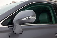 Het close-up van de zijspiegel van het autolichaam met chroomelementen in het ontwerp van een grijze sedan kleurt nat asfalt op d stock foto