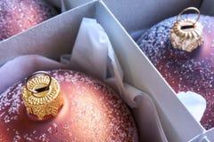 Het close-up van een groep brons kleurde Kerstmisballen in een kartondoos Stock Fotografie