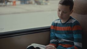 Het close-up van een jonge schooljongen die door bus wordt geschoten door stad reizen en leest een boek dat stock video