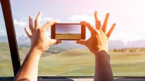 Het close-up van een jonge toerist in auto maakt een foto royalty-vrije stock afbeeldingen