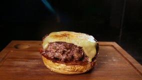 Het close-up van een kok met een cheddar van de open-vlambrander wordt gesmolten op een vleesballetje Voorbereiding van een hambu stock video
