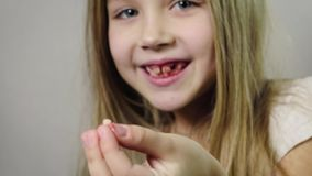 Het close-up van een leuk glimlachend meisje, een kind die een gescheurde melkhoektand in haar hand en het aftappen tonen gomt, k stock video