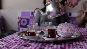Het close-up van een man hand giet thee van de ketel zwarte thee in kom stock video